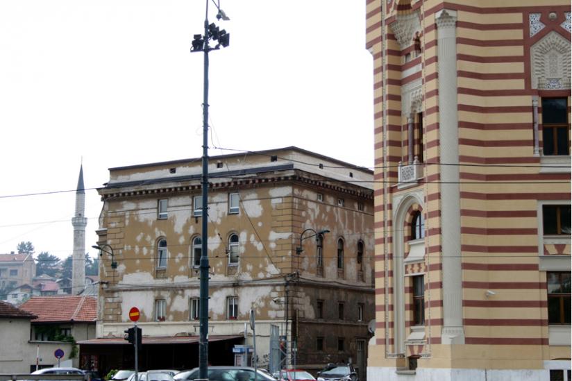 Neben der frisch renovierten Vijećnica verwittert ein Wohngebäude vor sich hin. Im Hintergrund das Minarett einer frisch renovierten Moschee.