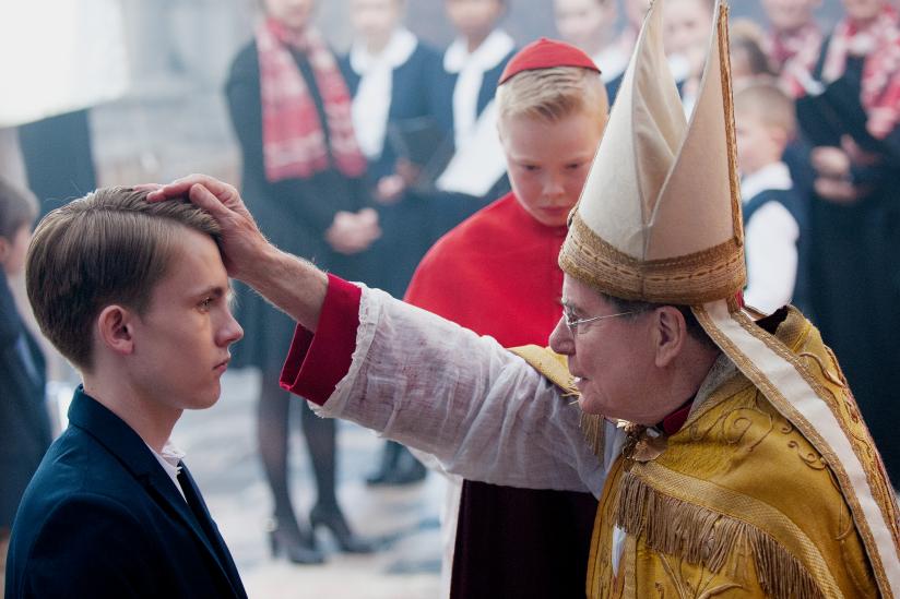 Kardinal Barbarin (François Marthouret) bei der Firmung von Alexandres Sohn Gauthier Guérin (Max Libert)