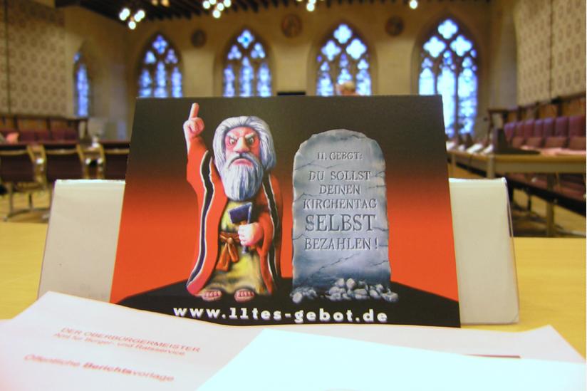 """Die Kunstaktion """"11. Gebot: Du sollst deinen Kirchentag selbst bezahlen"""" zeigt Wirkung im Rat von Münster"""
