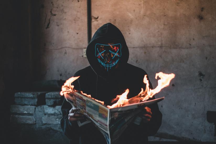 Ein vermummter Mensch liest eine brennende Zeitung