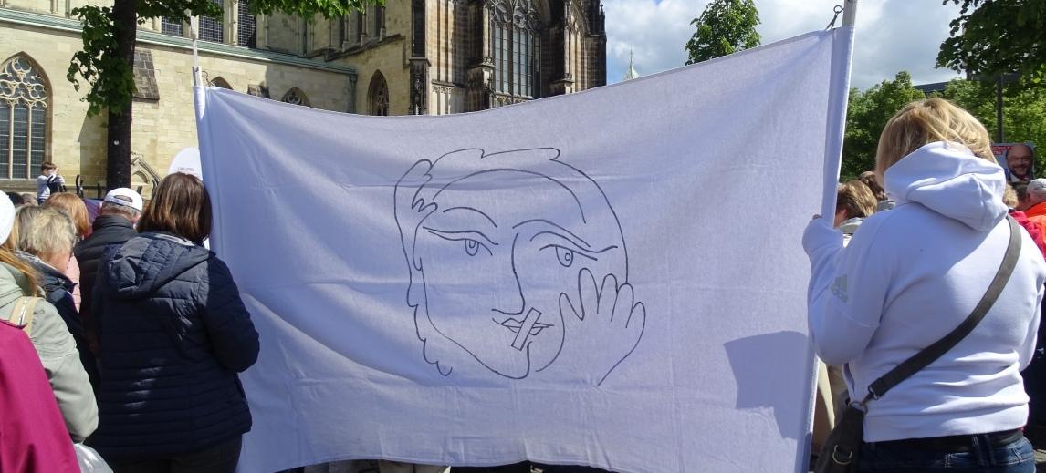 Streikende Katholikinnen mit stilisiertem Porträt einer Frau mit zugeklebtem Mund – dem Symbolbild der Initiative Maria 2.0.