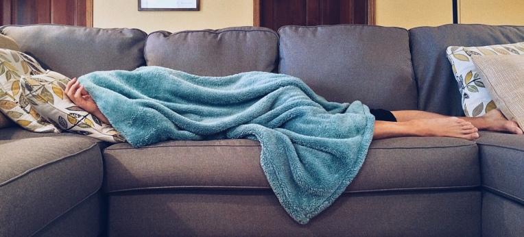 Frau liegt unter einer Decke auf dem Sofa