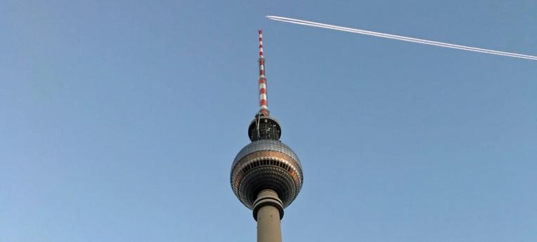 Ein Flugzeug fliegt in großer Höhe über den Berliner Fernsehturm. Der Verschwörungstheoretiker sieht hier Chemtrails.