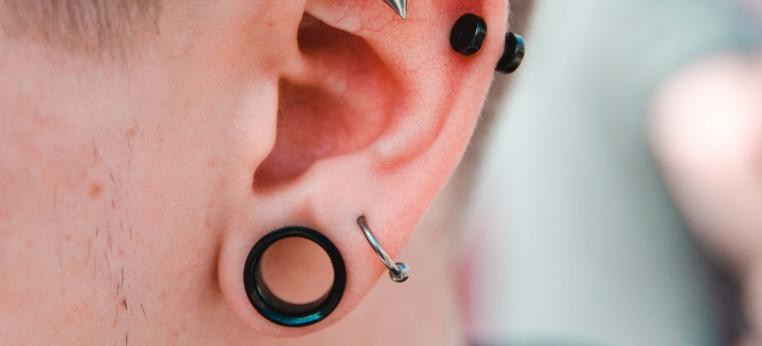 """Ohr geschmückt mit einem Ohrring, zwei Piercings und einem sogenannten """"Fleshtunnel"""""""
