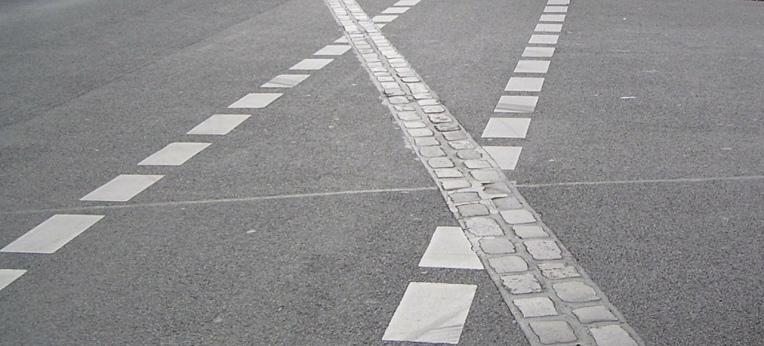 Nur noch diese Doppelreihe Pflastersteine erinnert an den Standort der Berliner Mauer.
