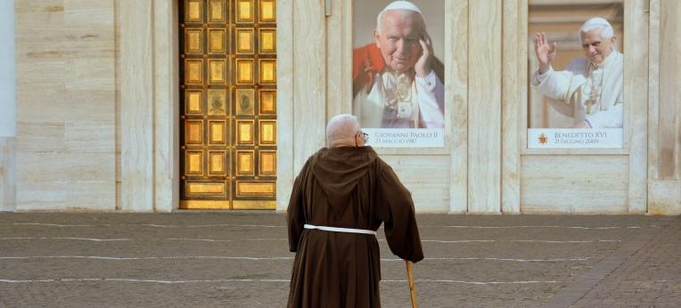 Ein Mönch vor den Bildern zweier Päpste.