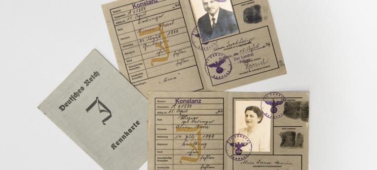 """Passpapiere der Familie Levinger mit dem 1938 eingeführten """"Judenstempel"""", einem gelben """"J"""" im Innern und einem schwarzen """"J"""" auf der Kennkarte."""