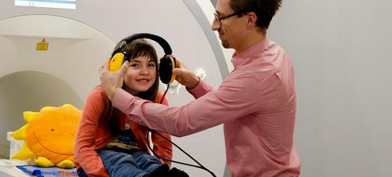 Mithilfe der Attrappe eines Hirnscanners bereitet sich eine junge Probandin auf ein Experiment vor.