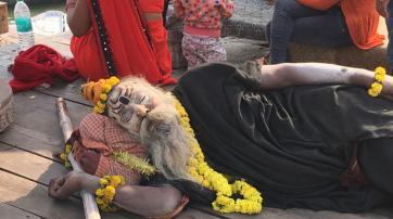 Ein mit Asche eingeriebener Aghori schläft am Ufer des Ganges.